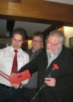 Dieter Stauber, Peter Lutat und der Jubilar Heinz Tautkus beim Studium der Ehrungsurkunde